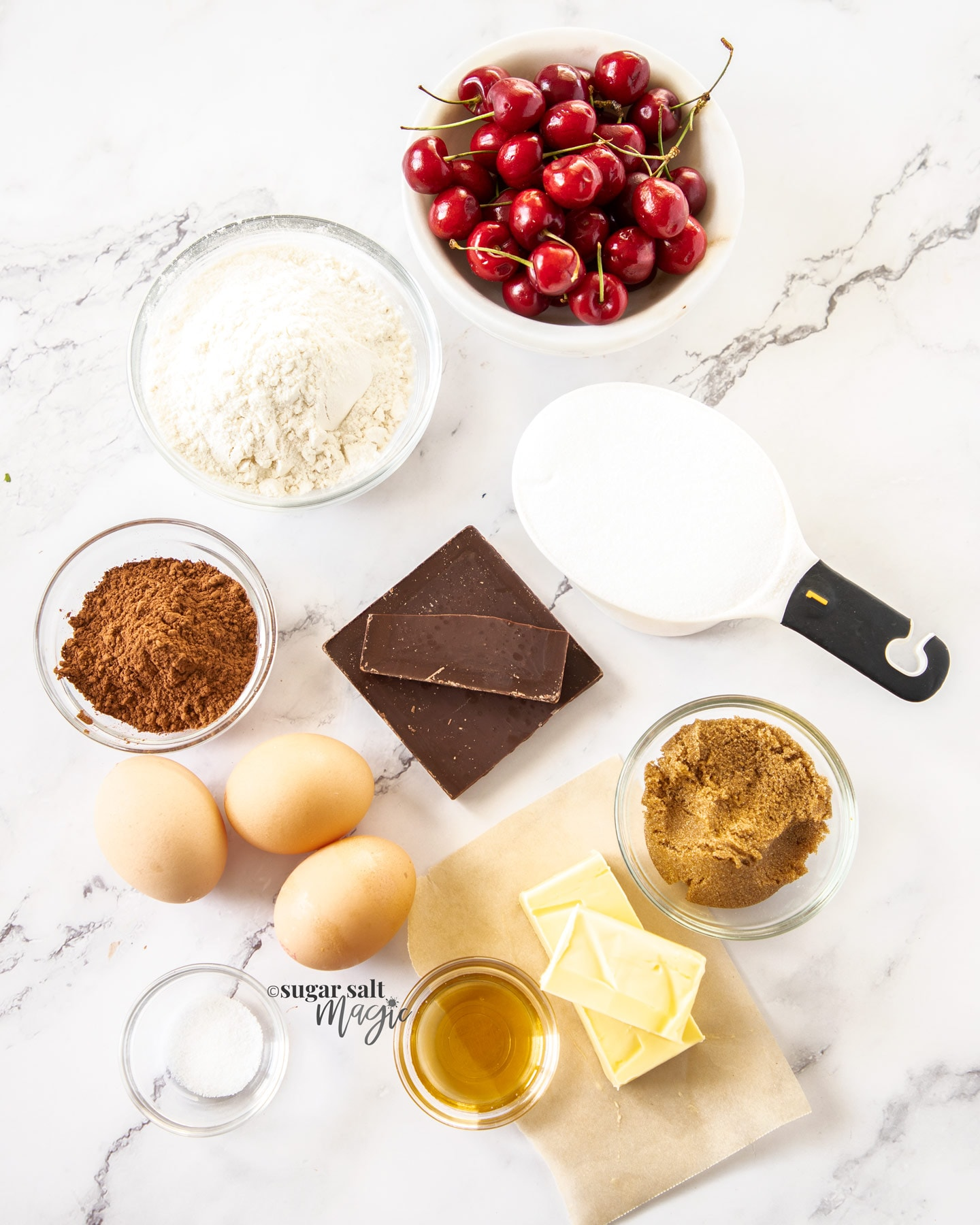 Ingredients for black forest brownies on a white marble surface