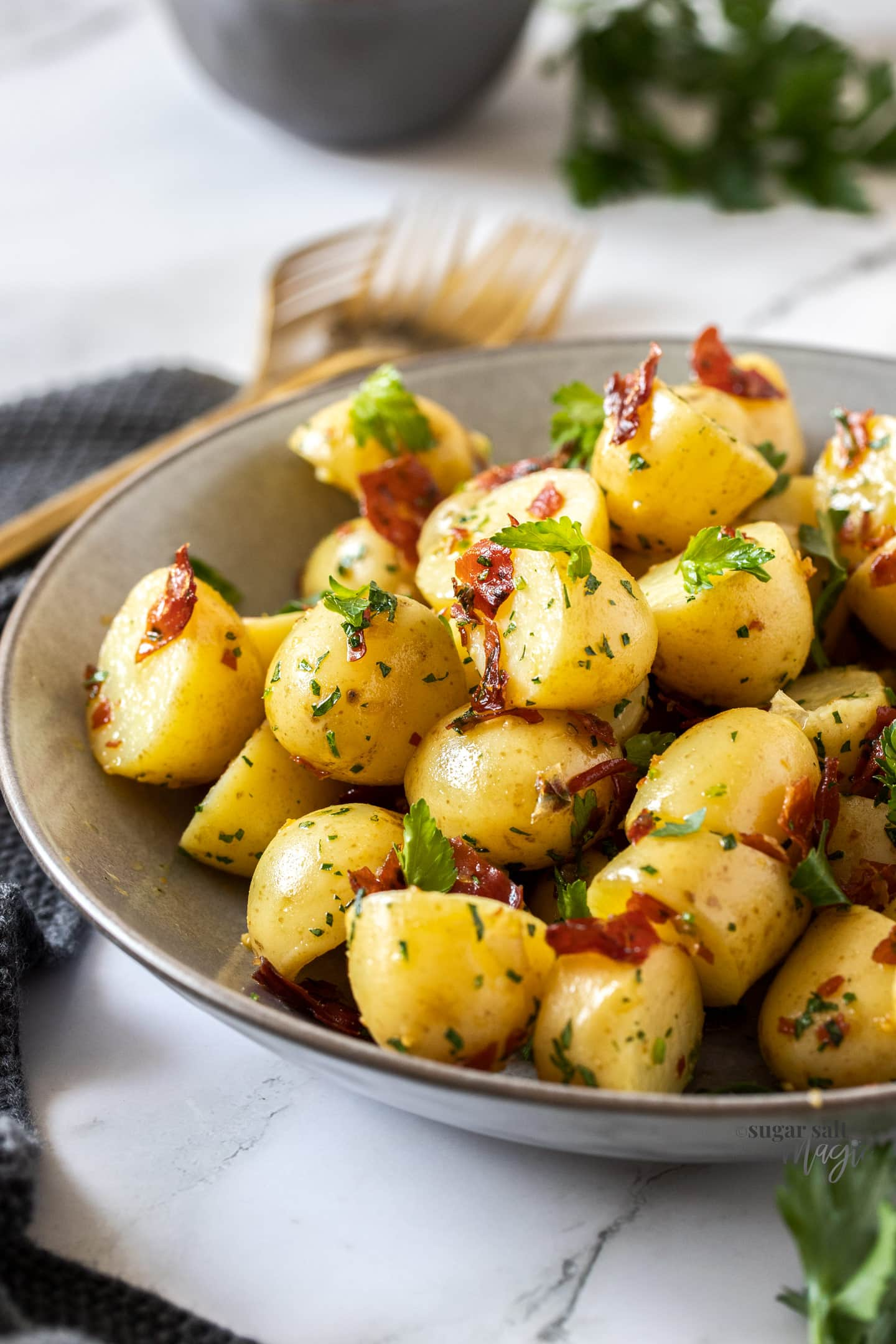 A grey bowl filled with cooked potatoes sprinkled with parsley and prosciutto