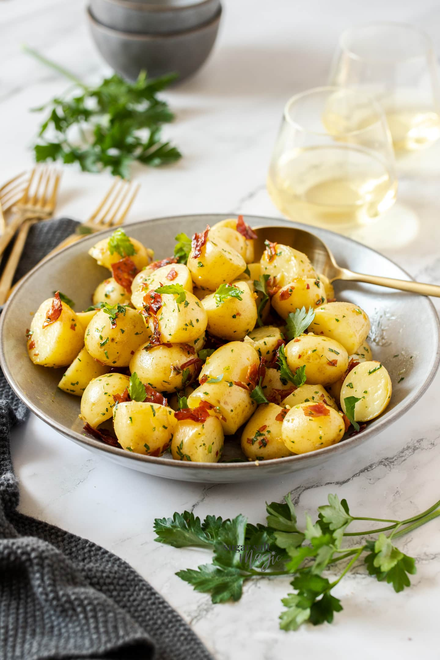 A large grey bowl filled with cooked potatoes with gold forks nearby