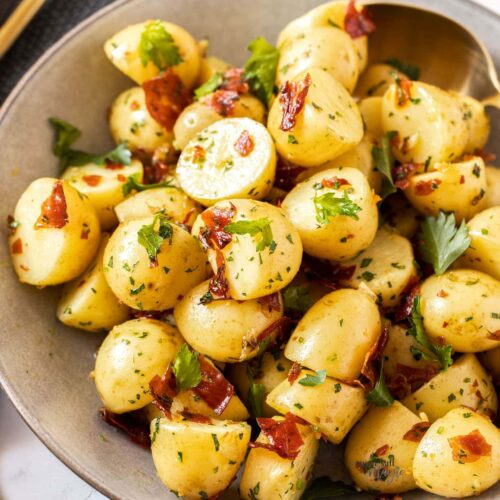 Closeup of a bowl full of cooked potatoes with pieces of prosciutto and parsley