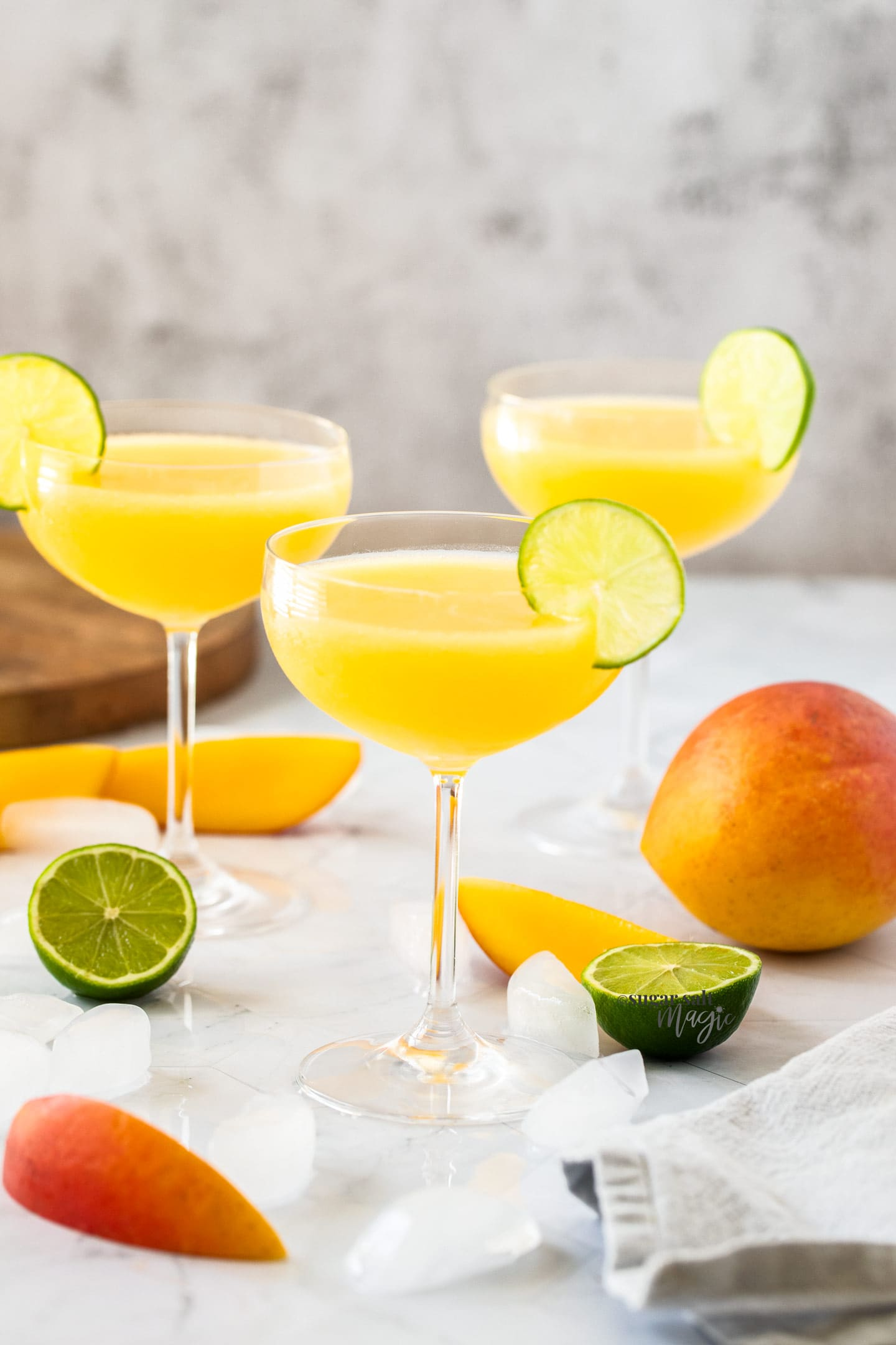 3 champagne saucers filled with mango daiquiri with a slice of lime on the edge
