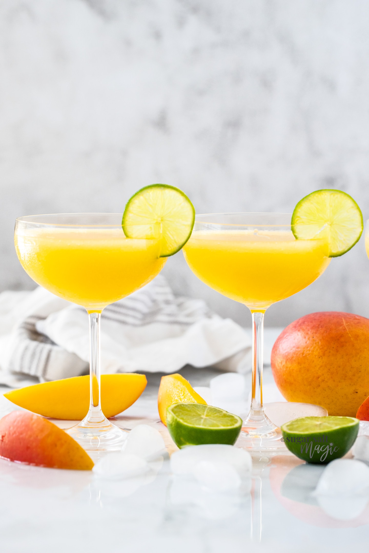 2 champagne saucers filled with mango daiquiri with a slice of lime on the edge