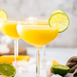 A champagne saucer filled with mango daiquiri with a slice of lime on the edge