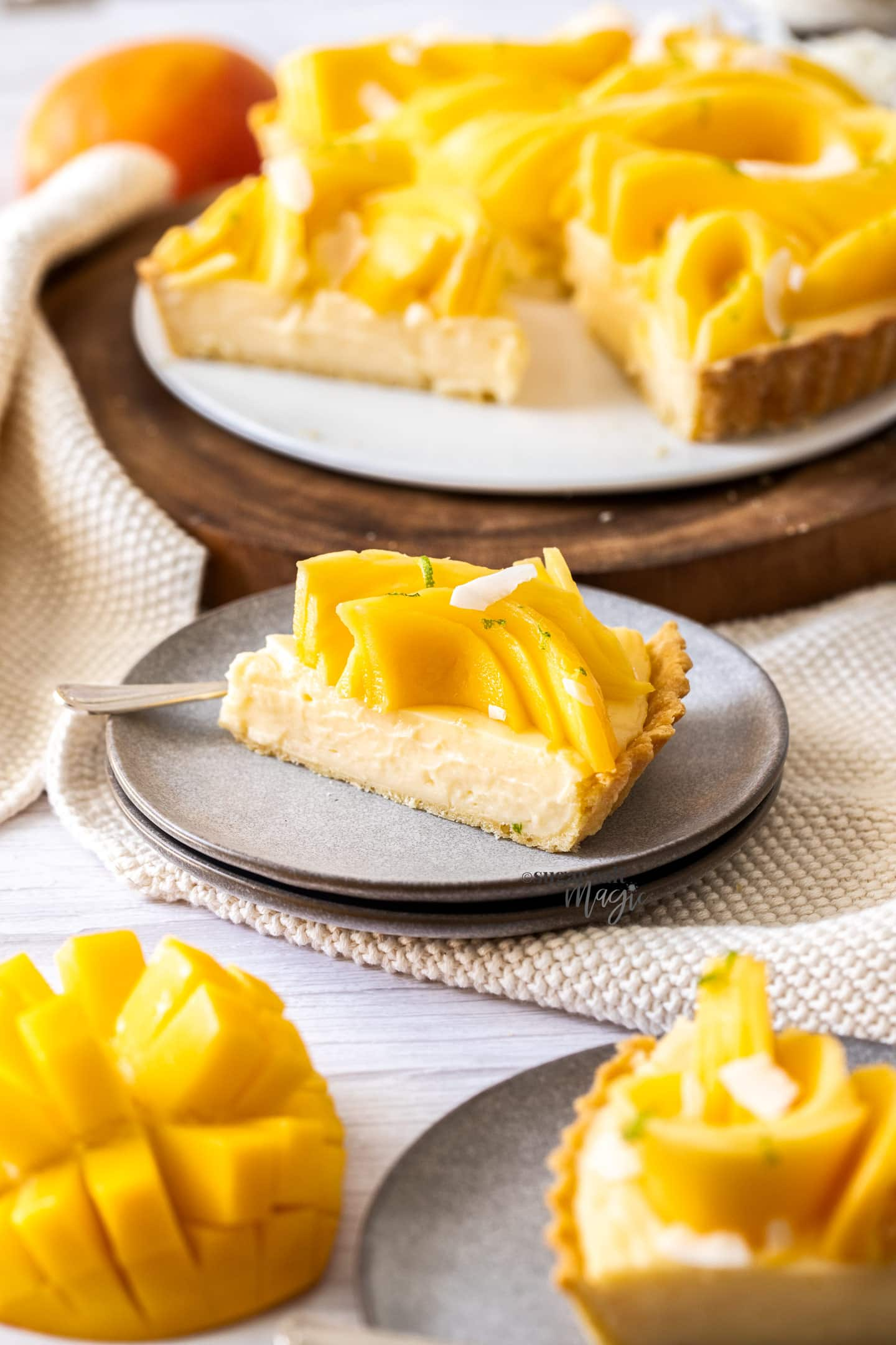 A slice of mango tart on a small grey plate