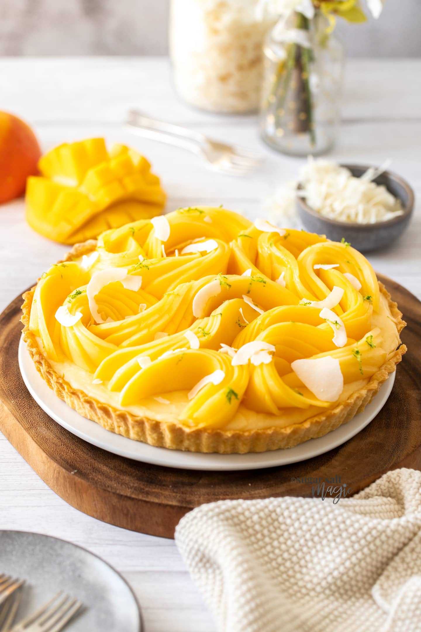 A tart topped with slices of mango on a wooden board