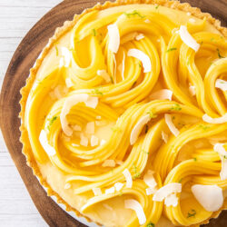 Top down view of a tart covered in sliced mango sitting on a wooden board