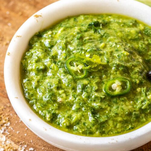 A white bowl on a timber board filled with green sauce