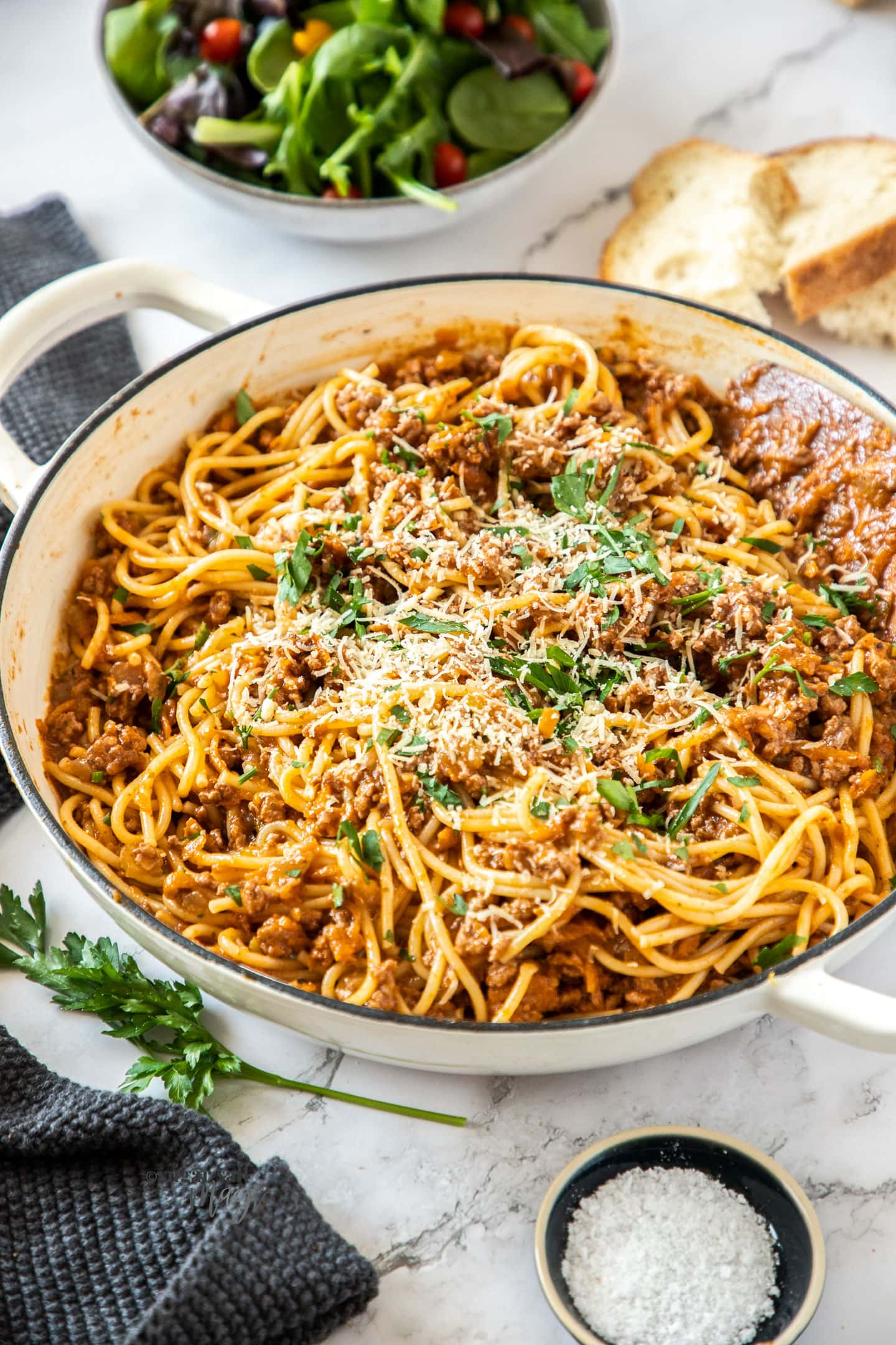 A white casserole dish filled with spaghetti bolognese