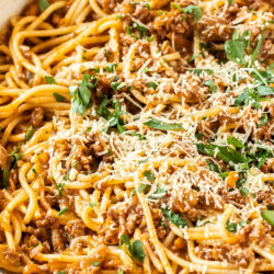Closeup of spaghetti bolognese in a white pan