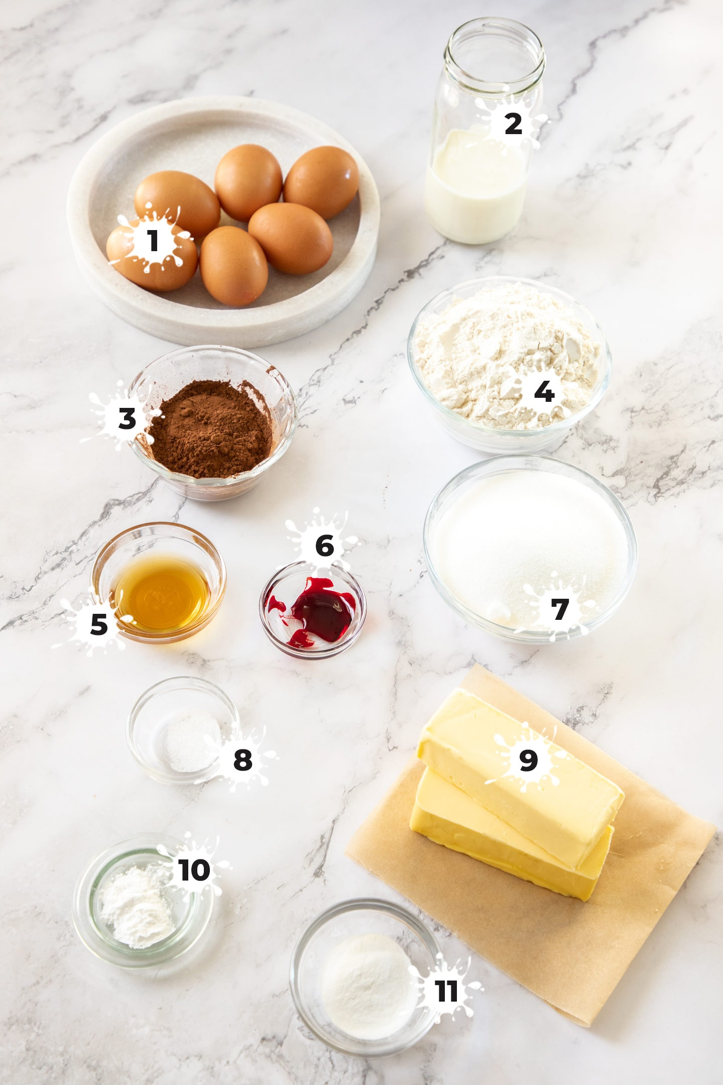 Ingredients for red velvet pound cake on a white marble surface