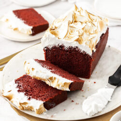 A red velvet loaf cake with bright white frosting