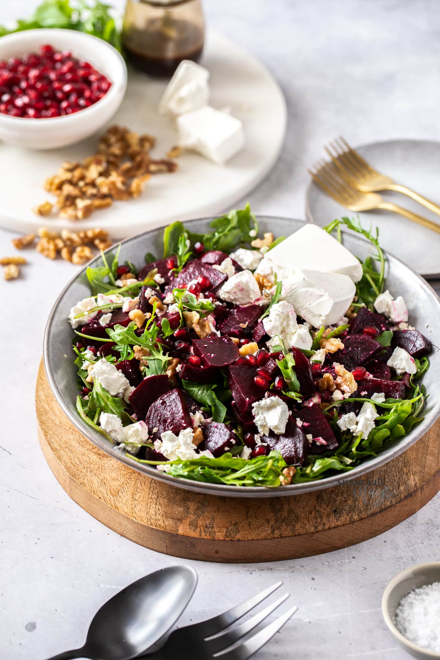 Beetroot, feta and salad leaves in a grey bowl on a wooden platter