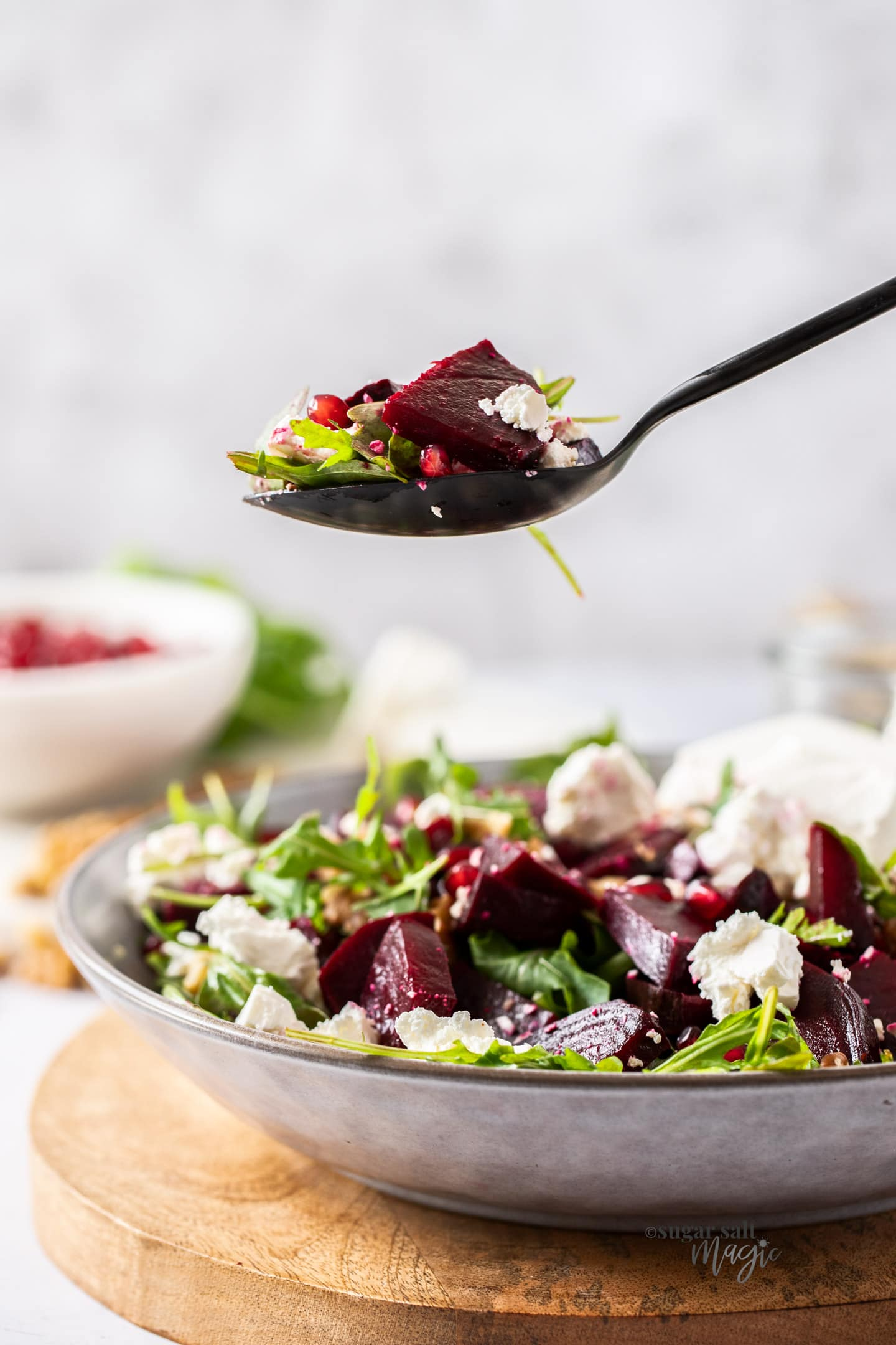 Beetroot and salad leaves on a black spoon hovering above a bowl of salad