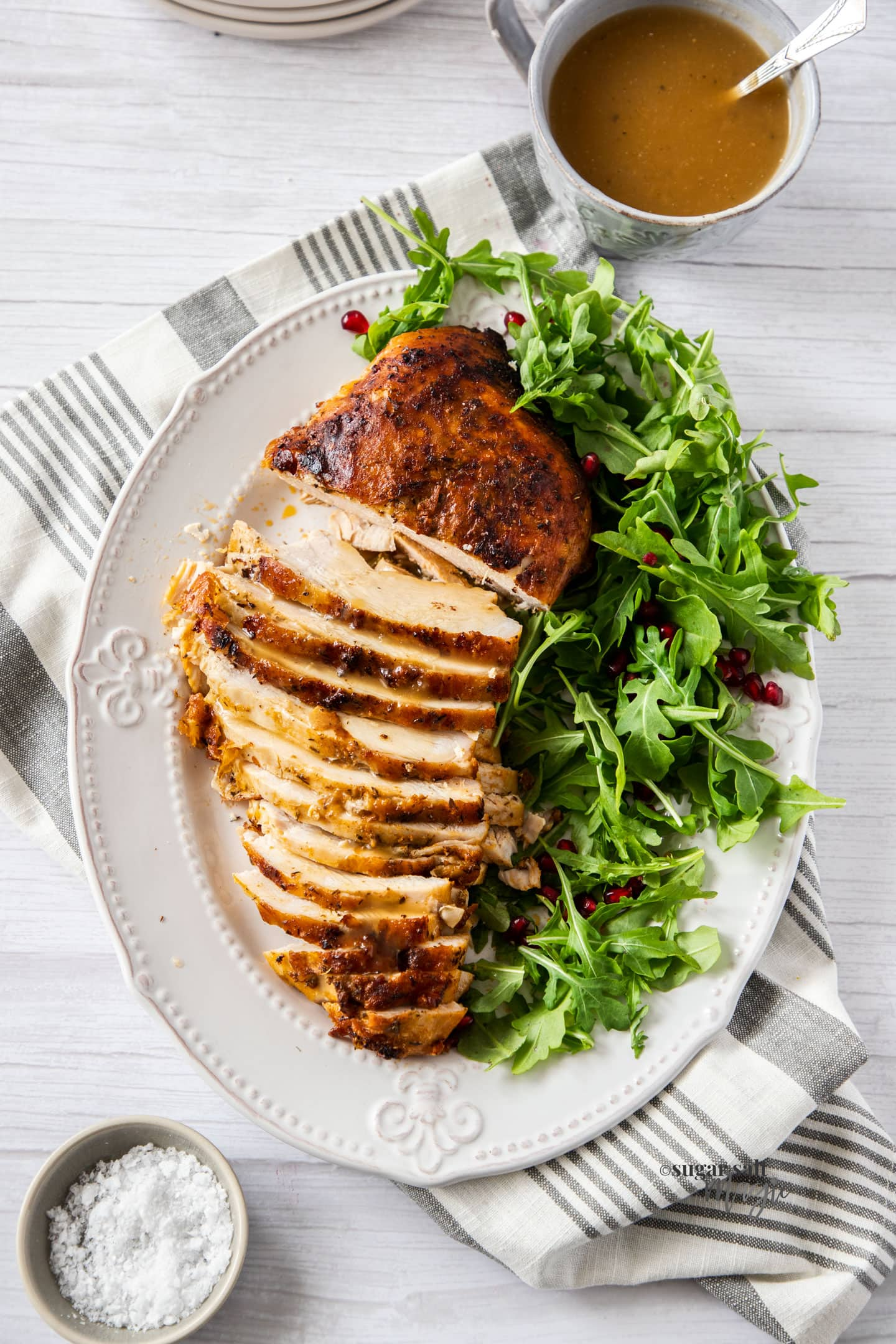 A golden turkey breast on a plate, partly sliced, with green salad on the side