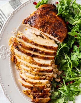 A golden turkey breast on a plate, partly sliced, with green salad on the side.