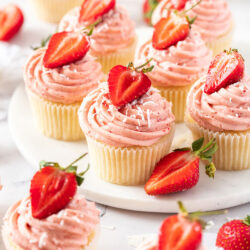 6 strawberry cupcakes on a white platter with a few more in front