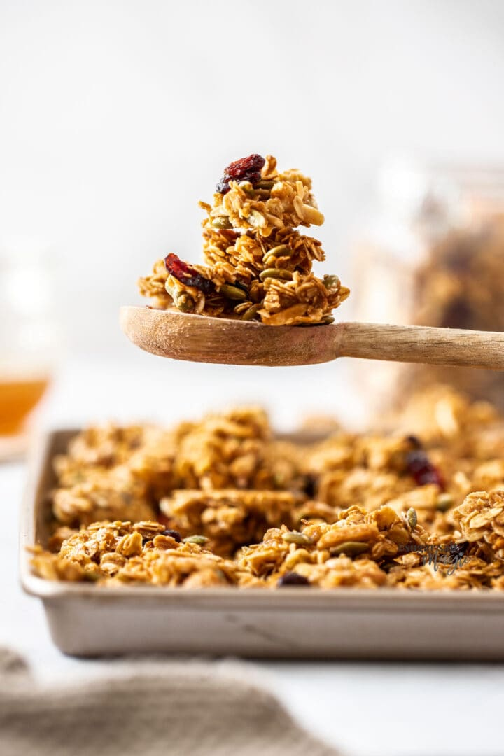 A spoon topped with chunks of granola