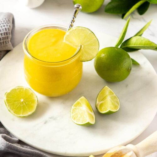 A glass jar filled with lime curd sitting on a white platter, surrounded by limes and eggs