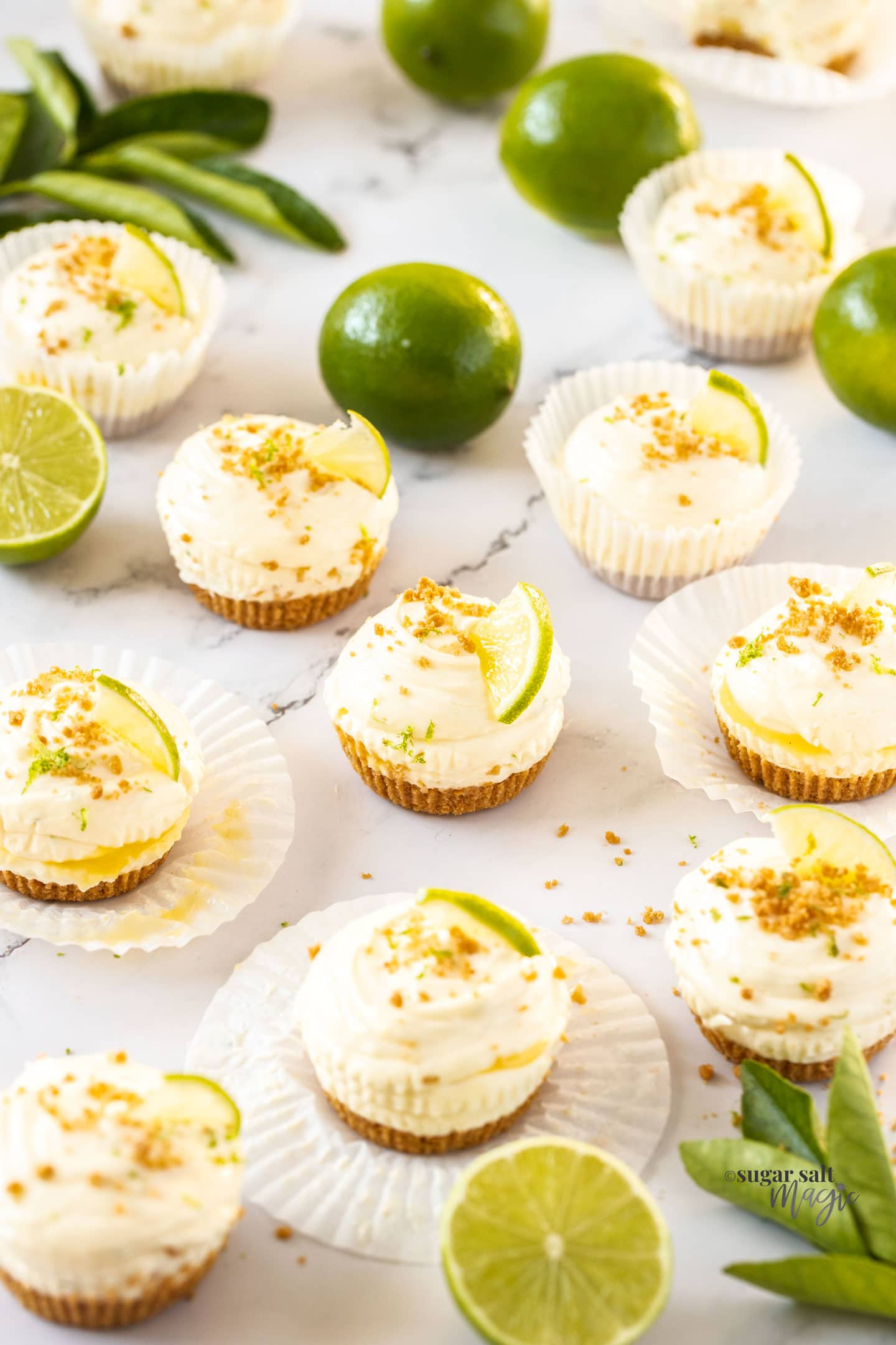A batch of mini cheesecakes surrounded by limes and cookie crumbs