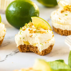 A mini lime cheesecake with a bite taken out and limes in the background