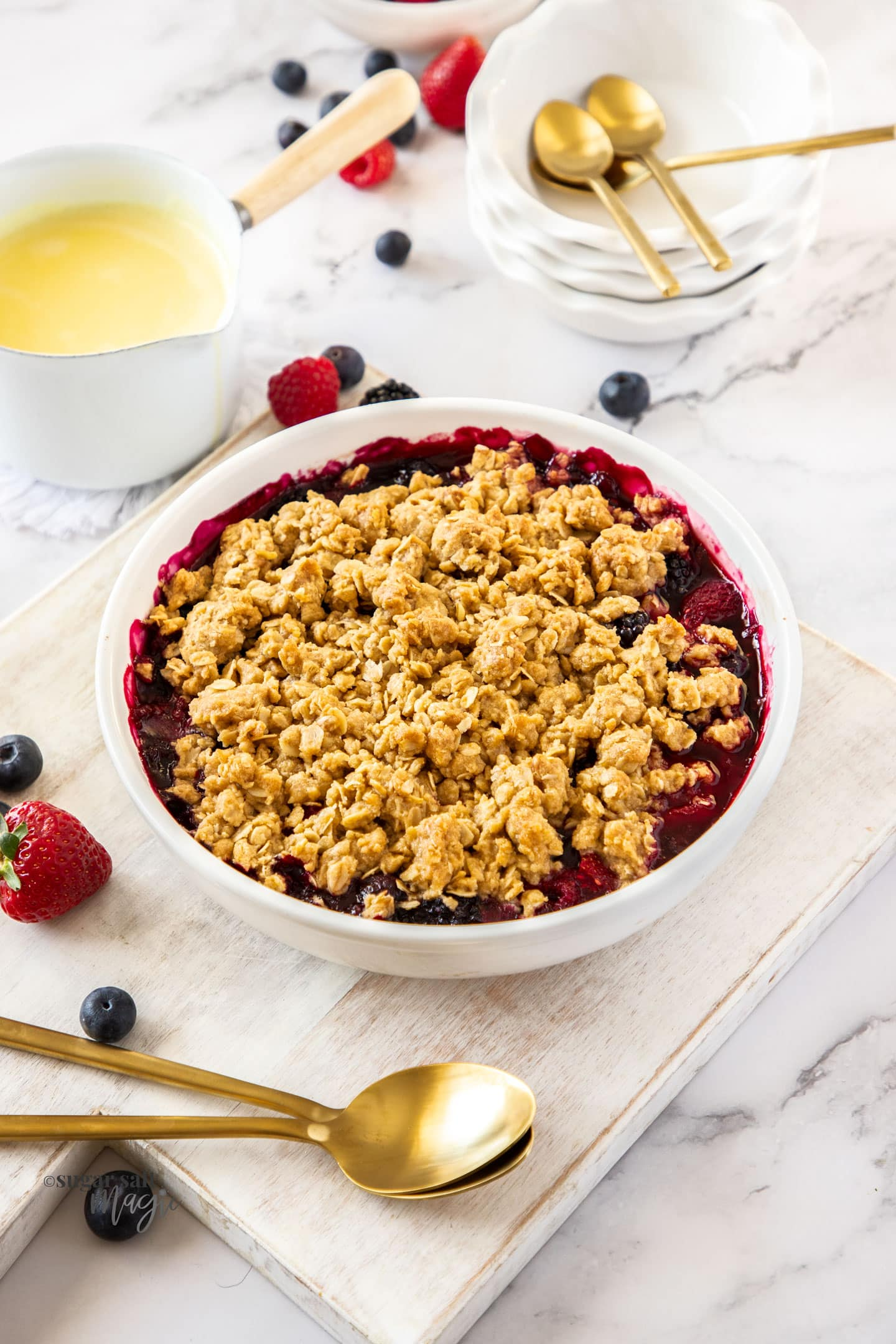 A white pie dish with berries under a crumble topping