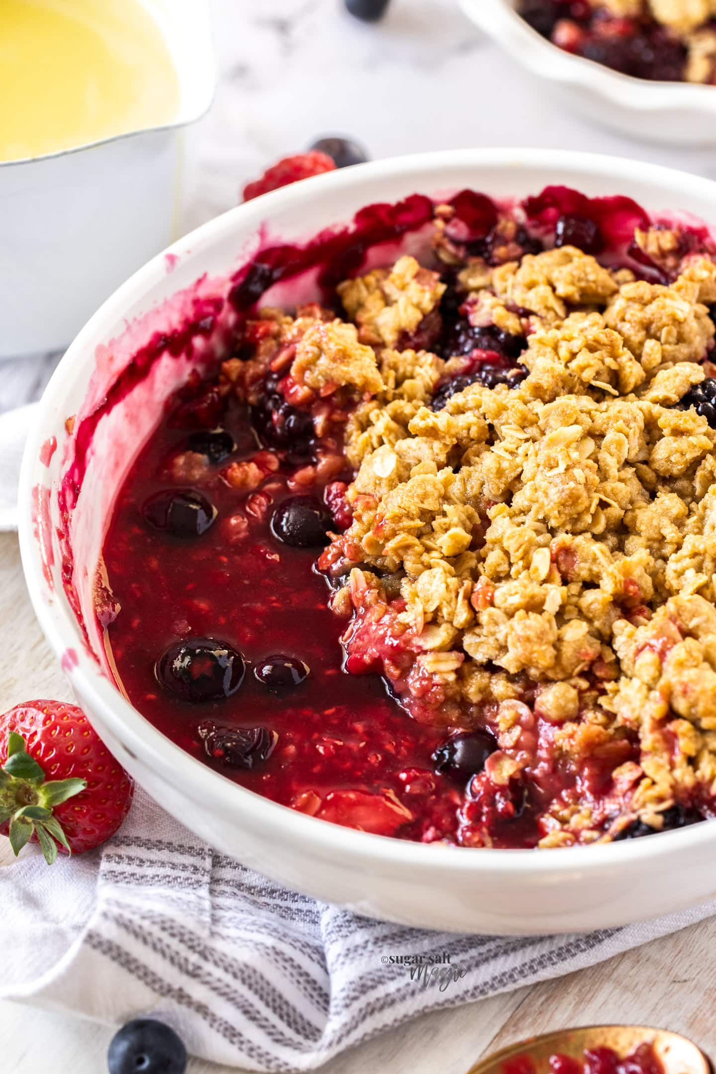 A white pie dish filled with berries in syrup and a crumble topping