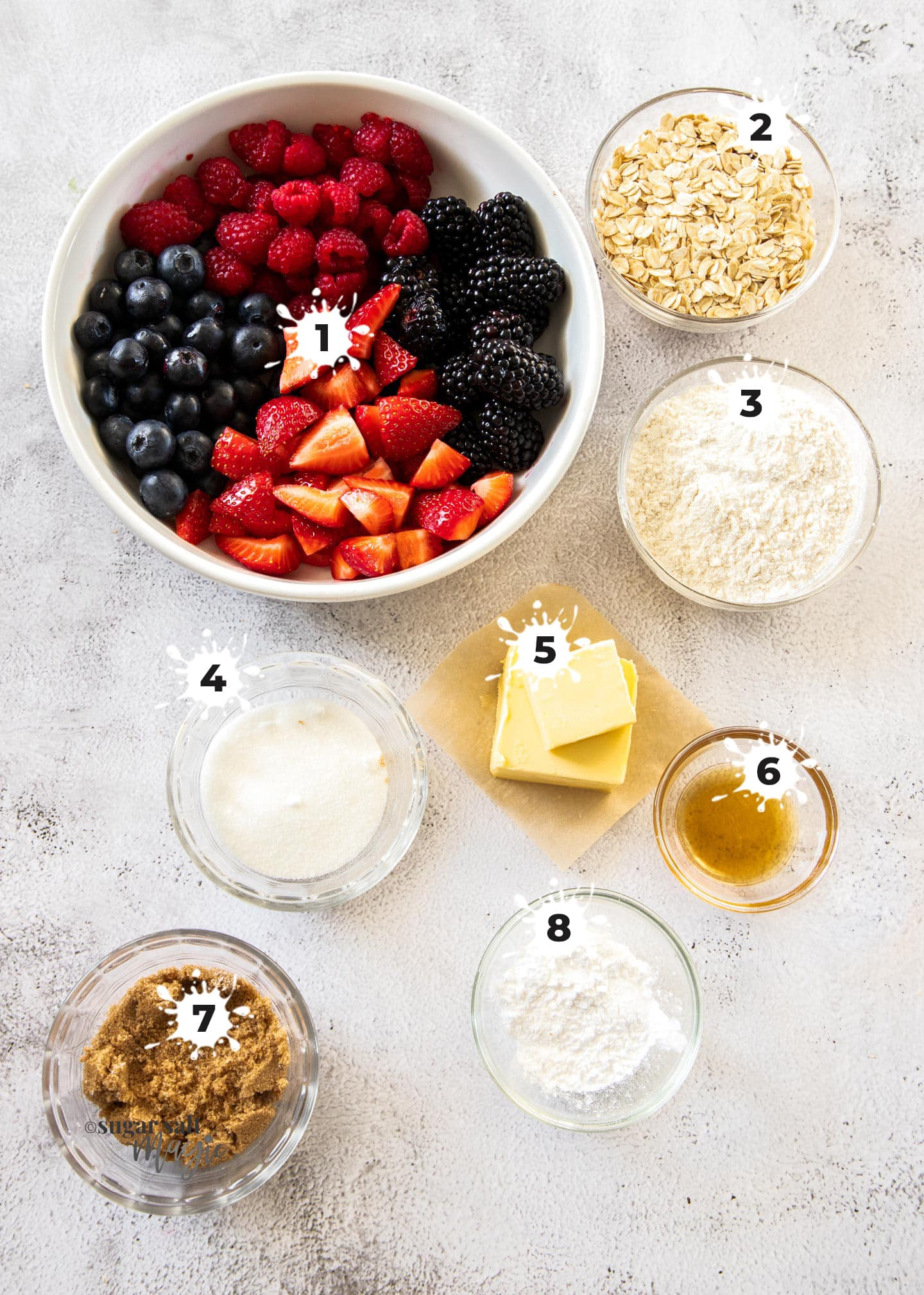 Ingredients for mixed berry crumble on a concrete benchtop