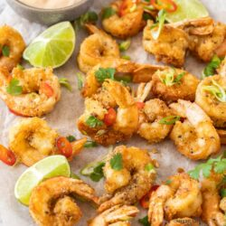 a batch fried prawns with chilli and green onion slices