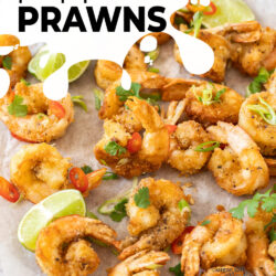 A batch of fried prawns on a sheet of paper with lime wedges