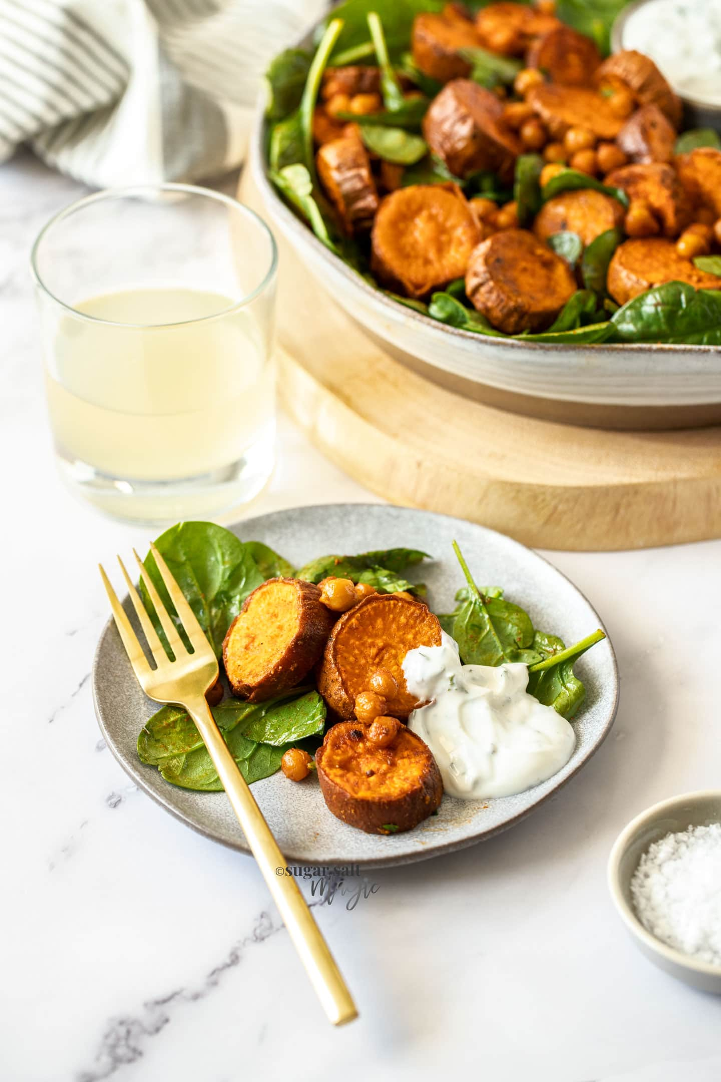 some sweet potato salad and yoghurt on a grey plate with a gold fork