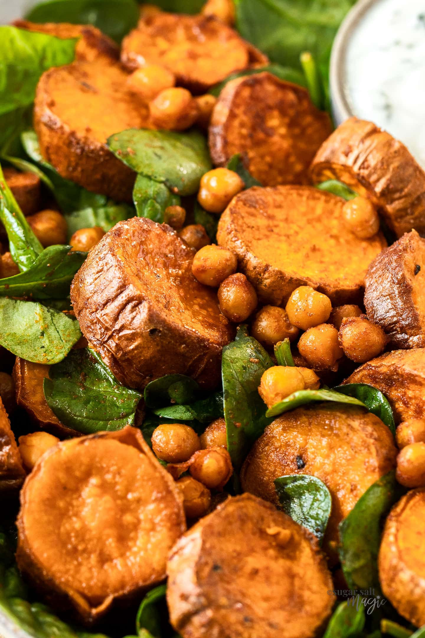 closeup of a salad of spinach, sweet potato and chickpeas