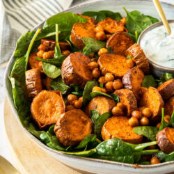 A white bowl filled with spinach and sweet potato on a wooden board