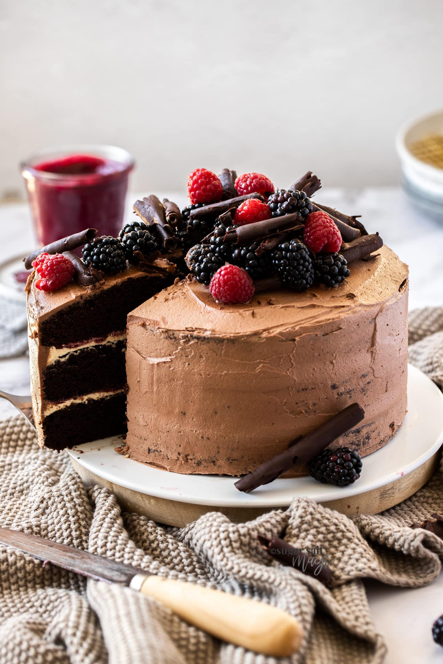 A 3 layer chocolate cake topped with berries adn chocolate curls