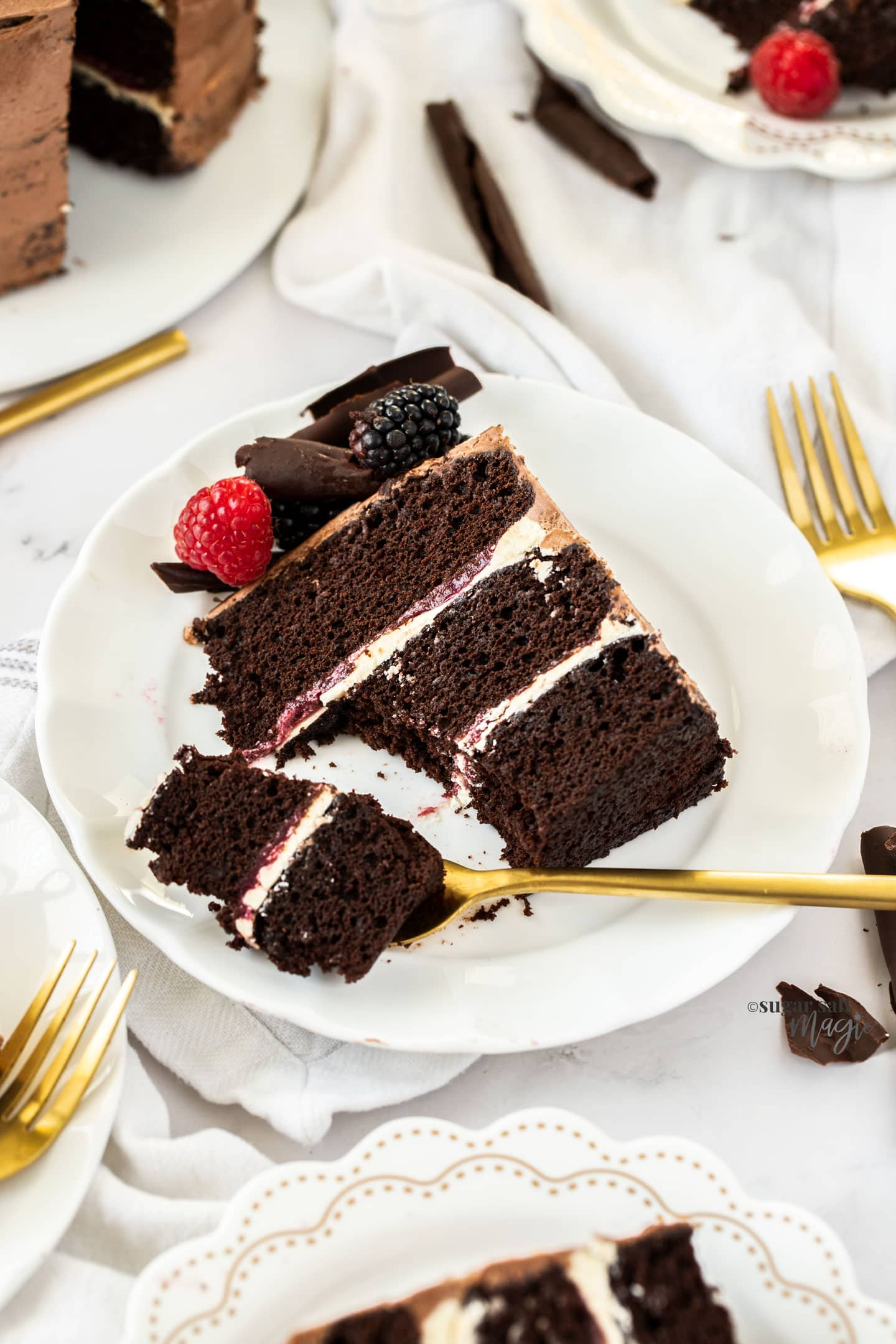A slice of 3 layer chocolate cake on a white plate with a forkful cut out