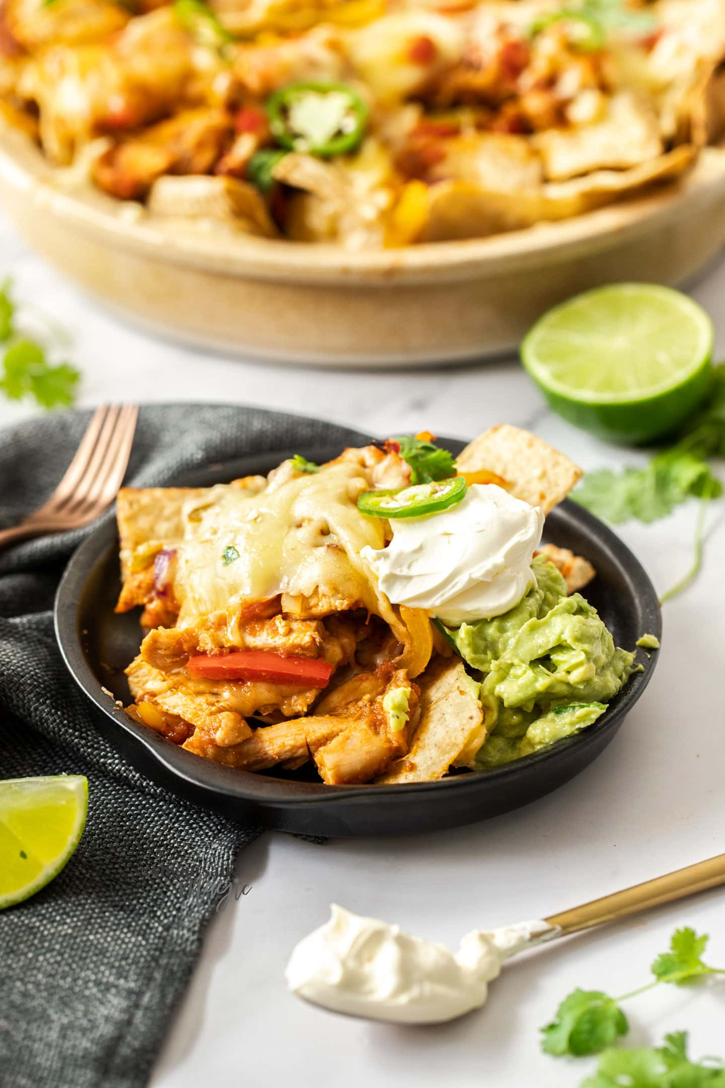 A black plate with nahcos, chicken and guacaomole on it