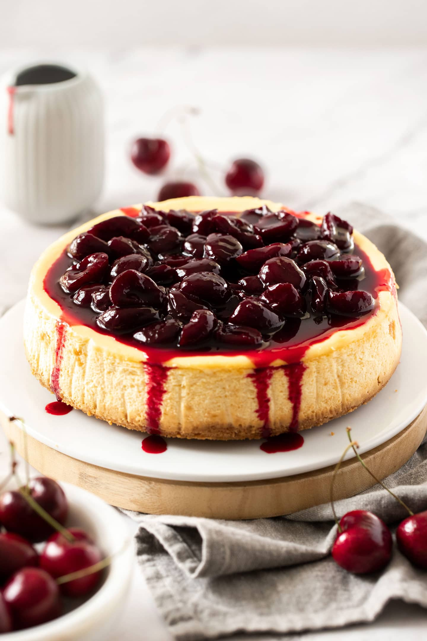 A cheesecake topped with cherry sauce on a white cake plate