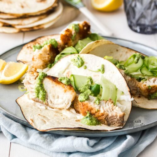 An open taco filled with fish and pesto on a grey plate