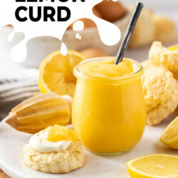 A glass jar filled with lemon curd with a scone sitting next to it
