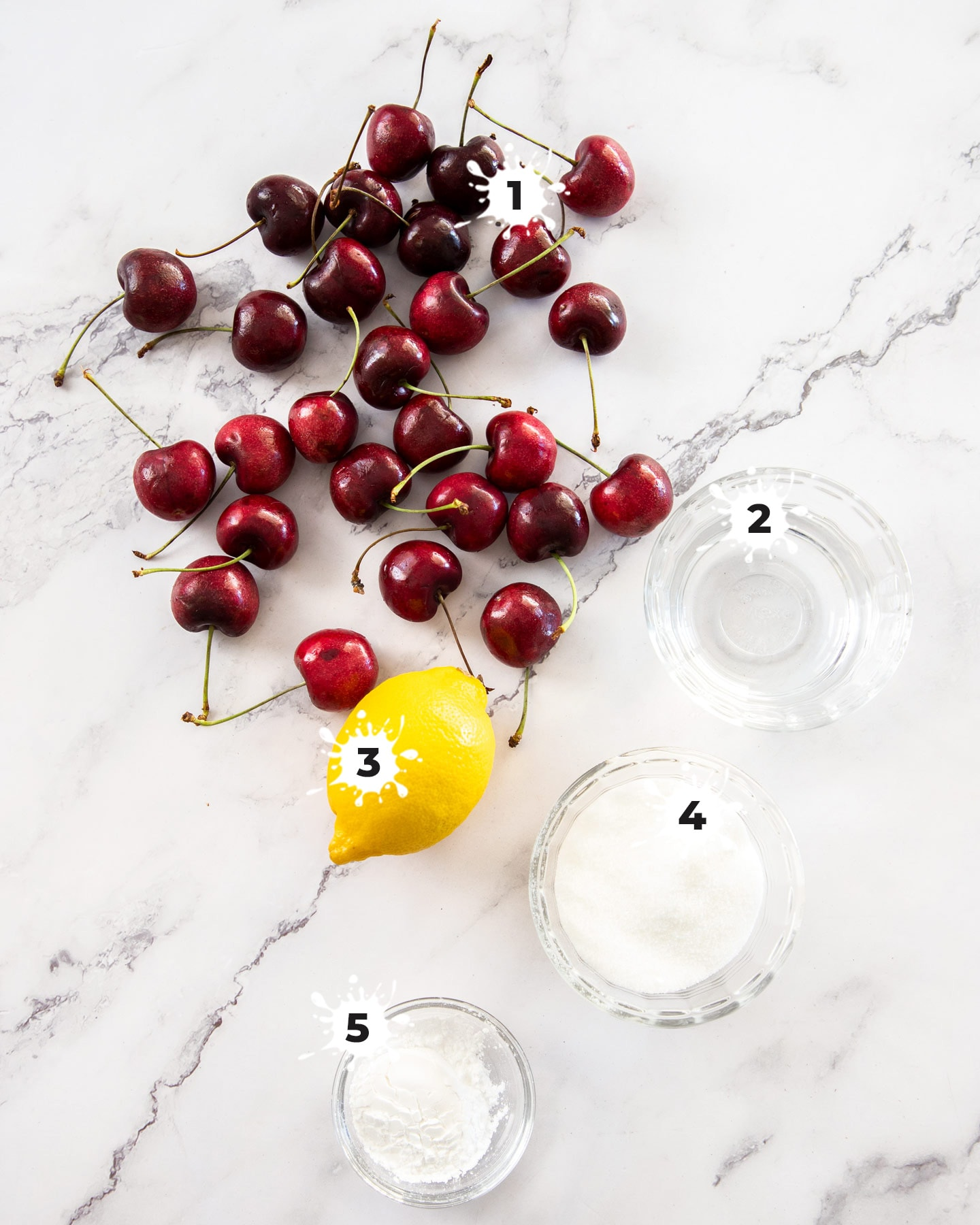 Ingredients for cherry sauce on a marble surface