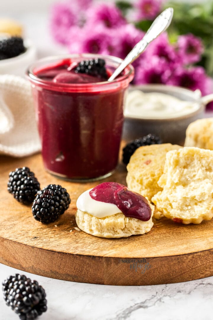 Half a scone topped with cream and blackberry curd on a wooden board