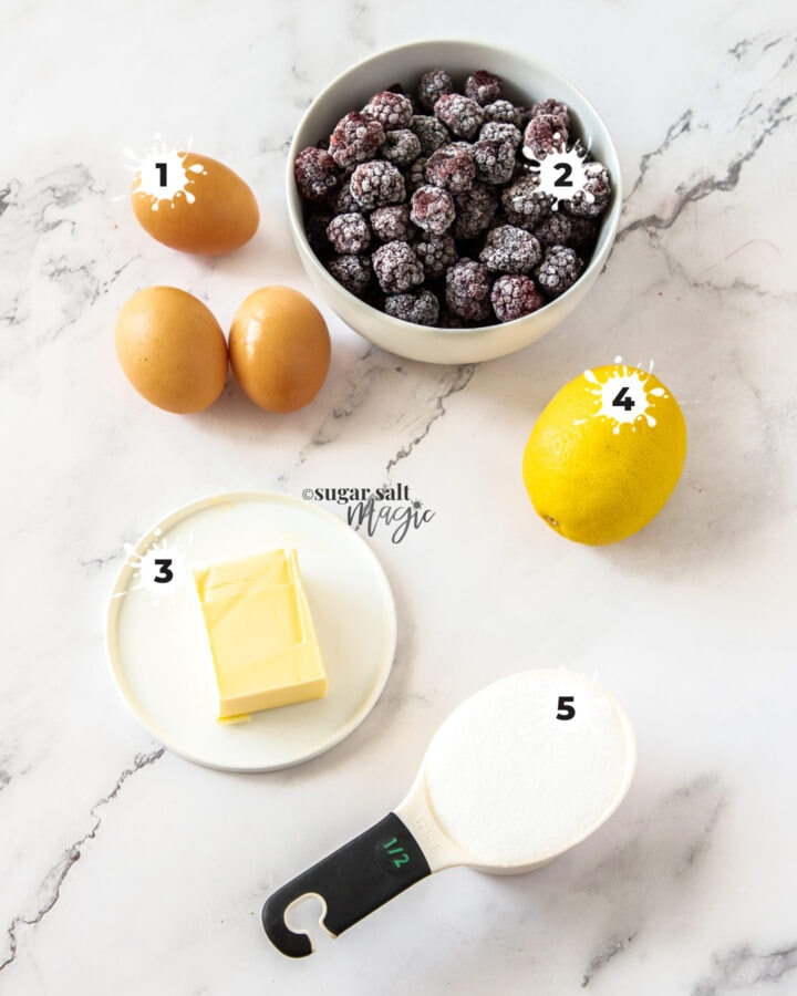 Ingredients for blackberry curd on a marble background