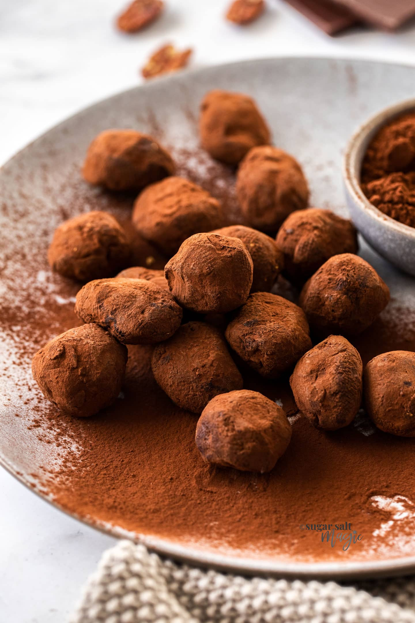 A pile of chocolate truffles on a grey plate