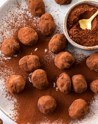 A batch of chocolate truffles on a plate with a small bowl of cocoa