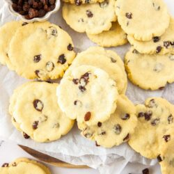 A pile of sultana filled cookies with a small bowl of sultanas.