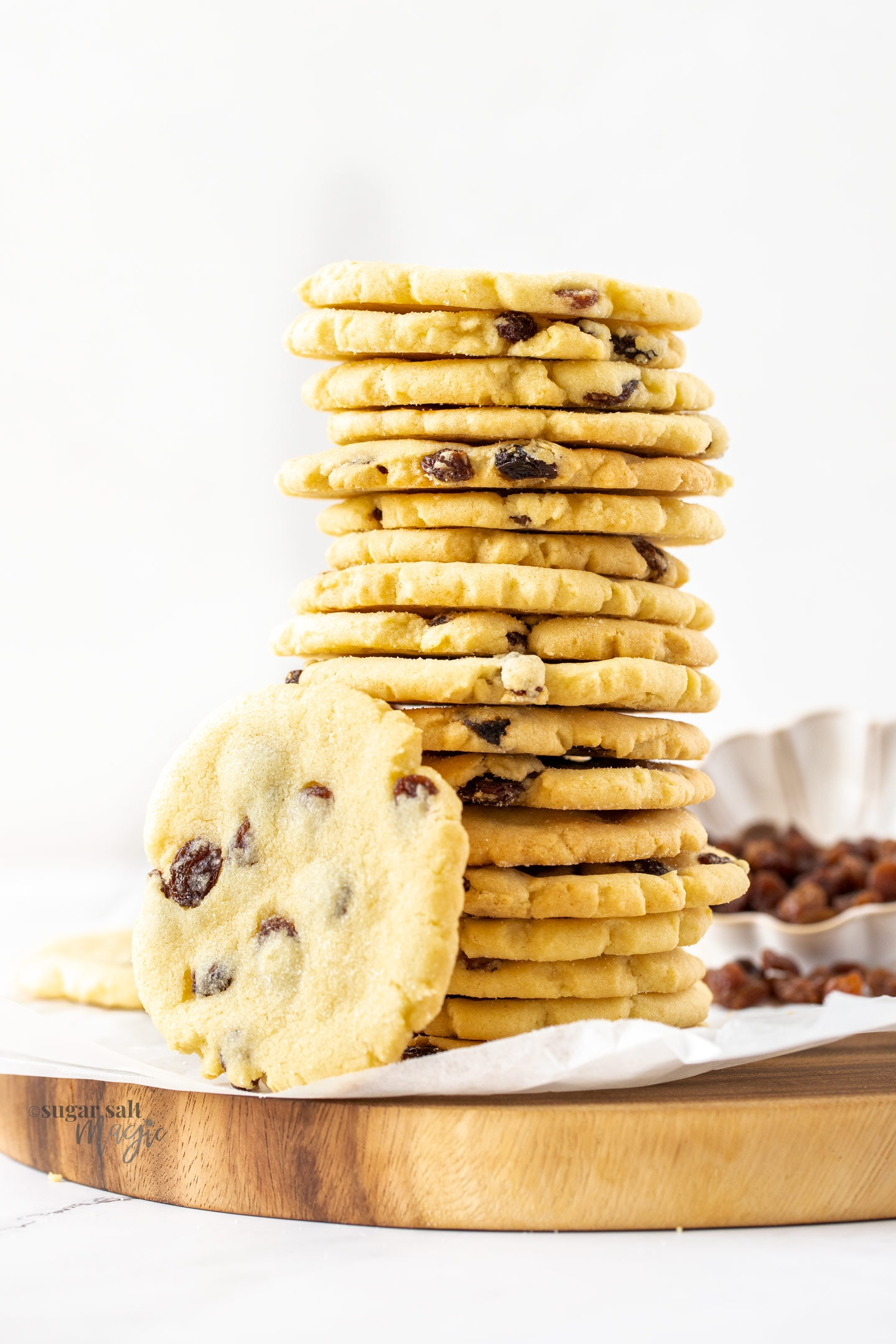 A very tall stack of sultana cookies on a wooden board.