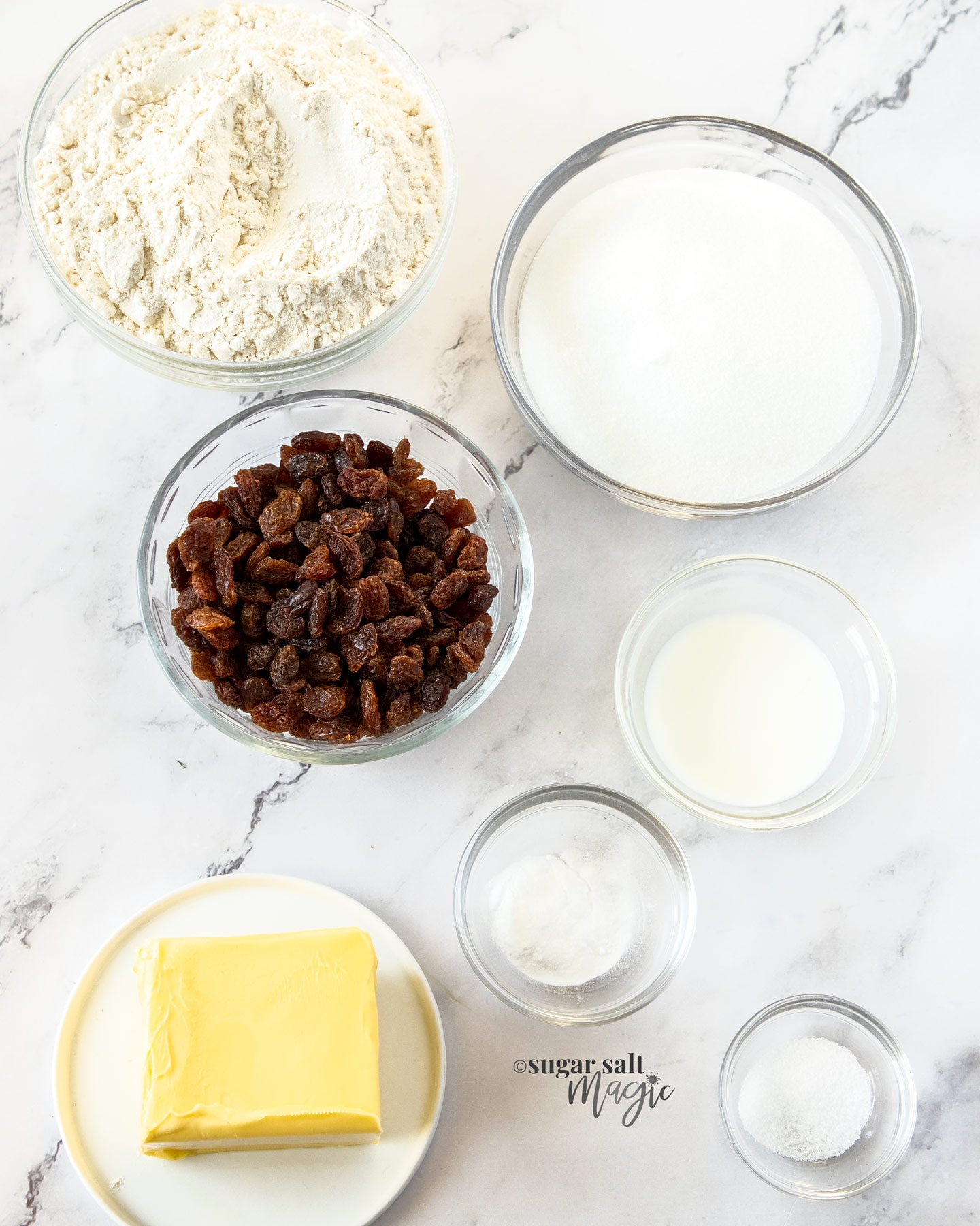 Ingredients for sultana cookies in glass bowls on a marble benchtop.