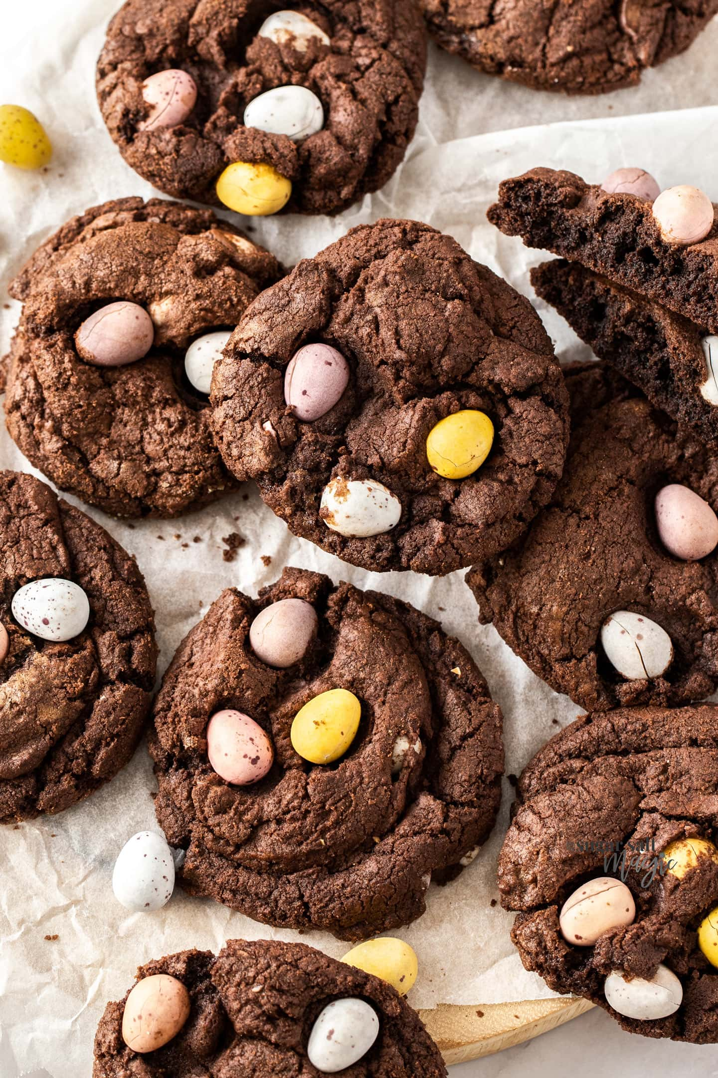 Closeup of a batch of chocolate cookies with Easter eggs in them.