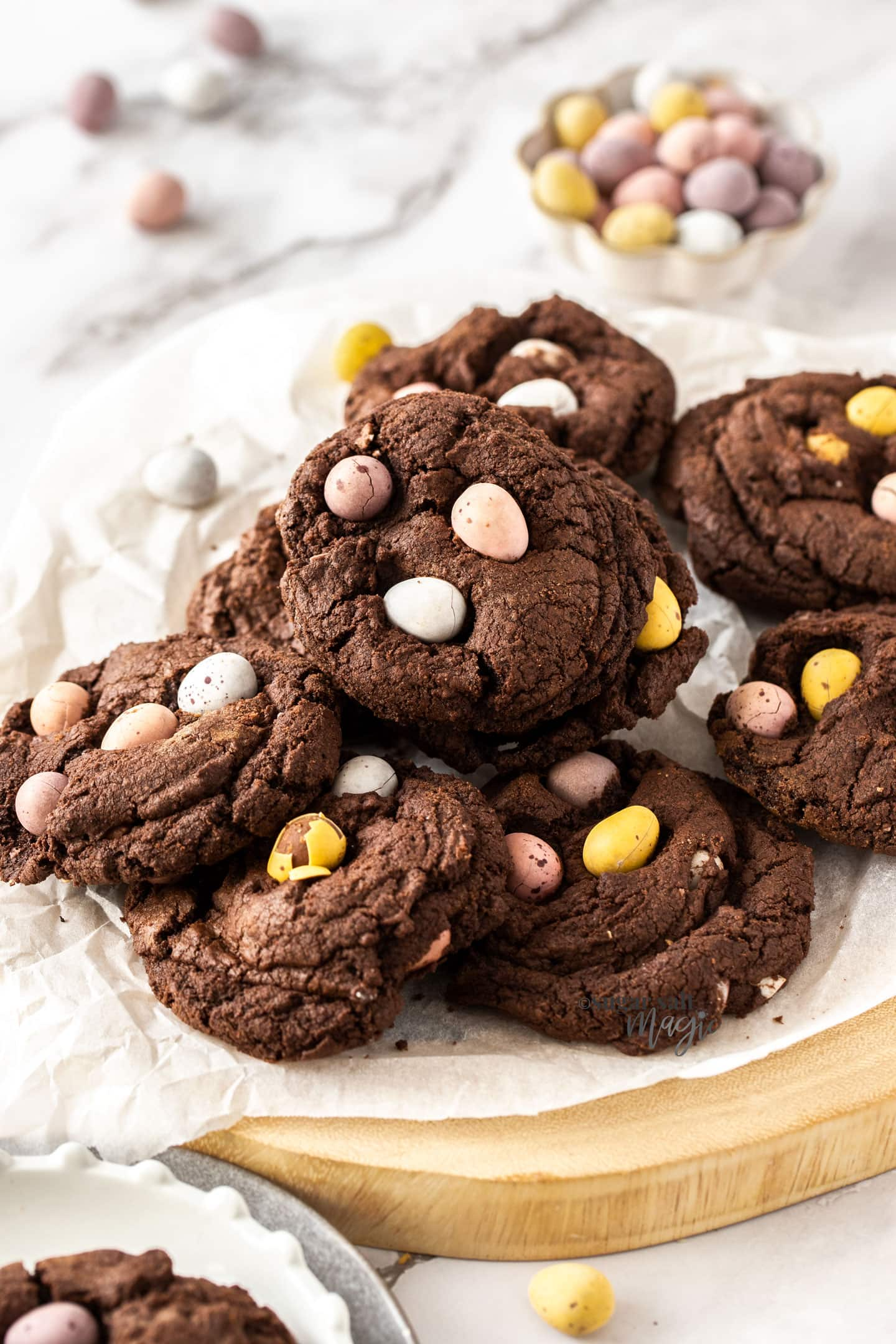 A batch of chocolate cookies on a wooden platter.