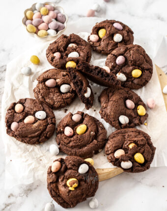 A batch of chocolate cookies on a wooden platter with mini eggs around.