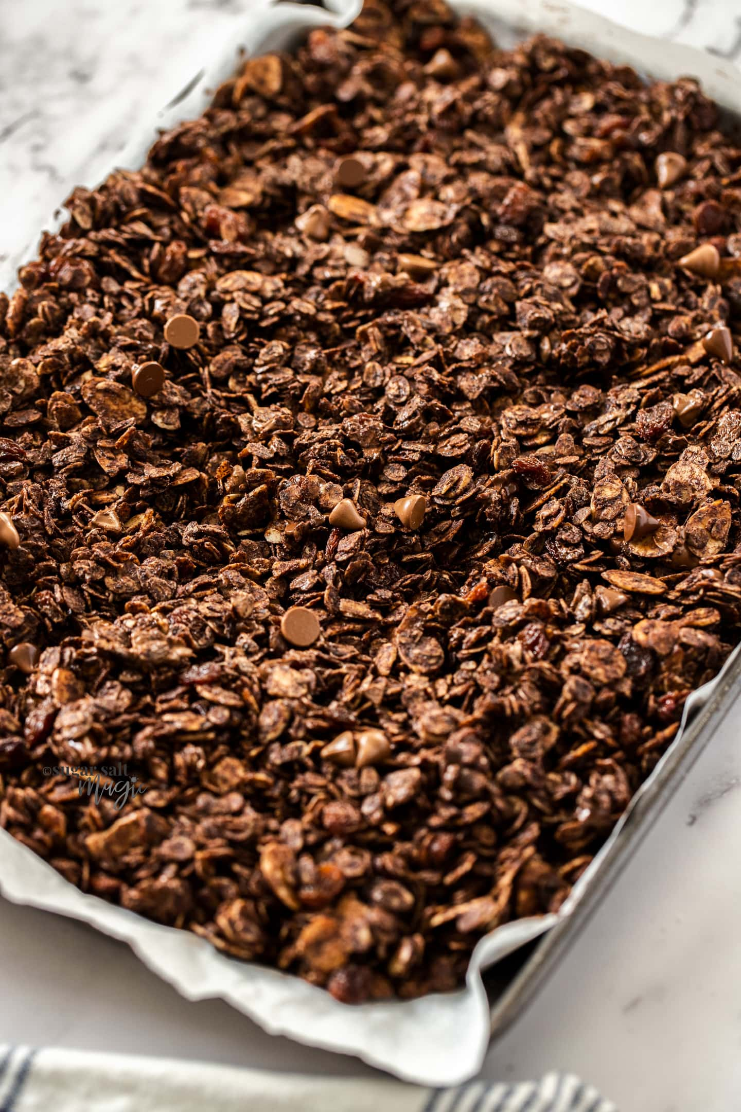 Closeup of chocolate granola on a baking tray.
